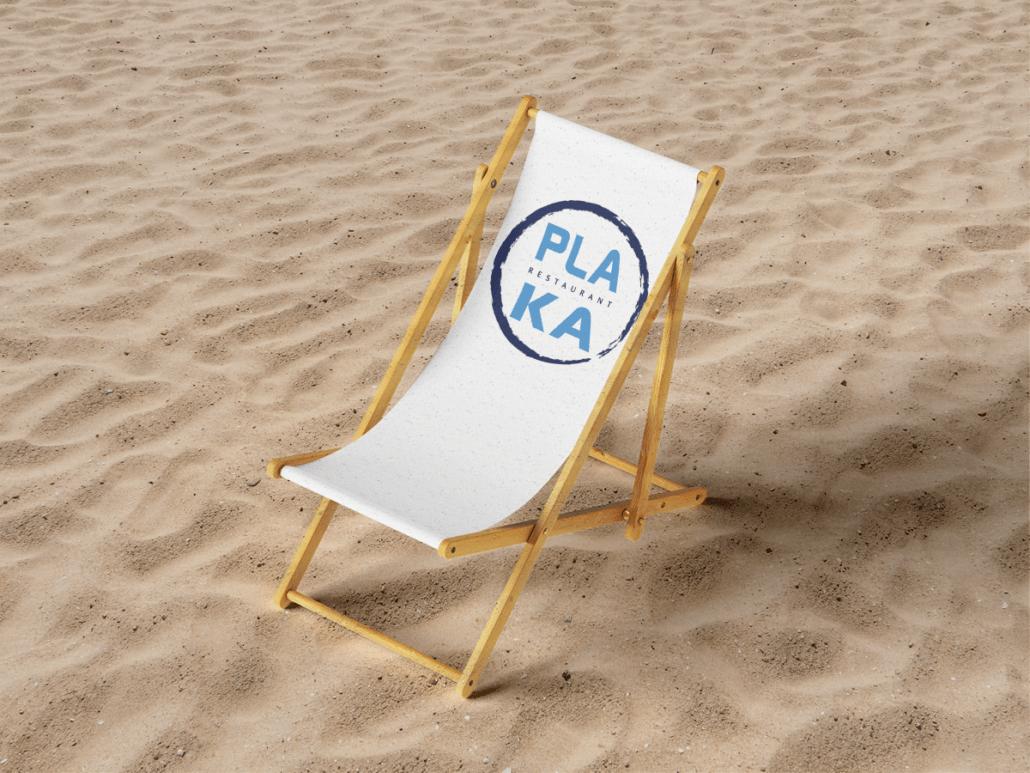 Chaise longue sur le sable avec logo Plaka